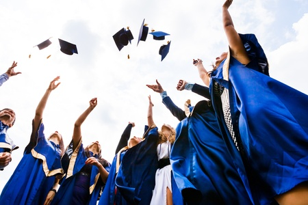toga: Imagen de feliz jóvenes graduados tirando sombreros en el aire