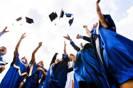 absolwent: Obraz szczęśliwych absolwentów rzucających kapelusze w powietrzu
