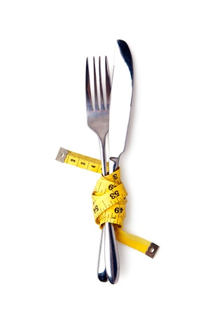 lightness: Measuring tape on a fork and knife - isolated over white Stock Photo