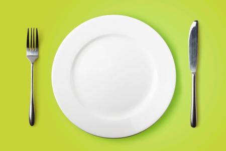 Lege plaat, vork en mes op groene achtergrond