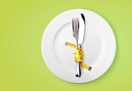 loose: Measuring tape on a fork and knife  - dieting concept image