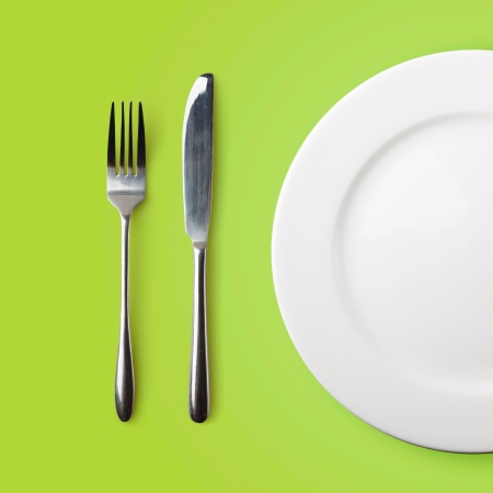 cooking ware: Empty plate, fork and knife on green background