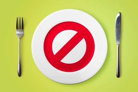 Empty plate with forbidden red sign, fork and knife on green background
