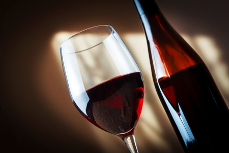 winy: Bottle and glass of red wine - studio shot Stock Photo