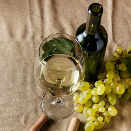 winy: Bottle and glass of white wine - studio shot Stock Photo