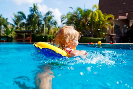 Little baby swimming in a pool on swimming ring photo