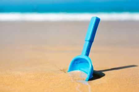Small shovel in the sand on the beach - concept image photo