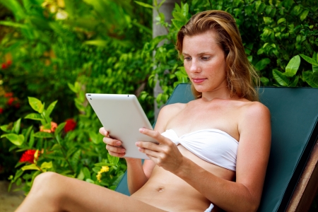 Beautiful young woman relaxing on sunbed with tablet photo