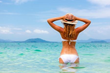 badpak: Mooie jonge vrouw in bikini op het zonnige tropische strand ontspannen in het water