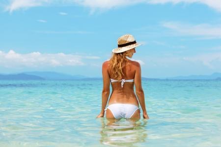 Beautiful young woman in bikini on the sunny tropical beach relaxing in water 免版税图像