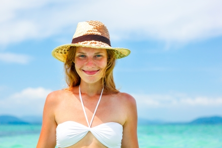 Portrait of Beautiful young woman in hat on the sunny tropical beach photo