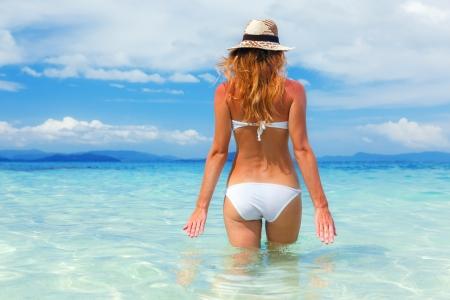 beach girl: Beautiful young woman in bikini on the sunny tropical beach relaxing in water Stock Photo