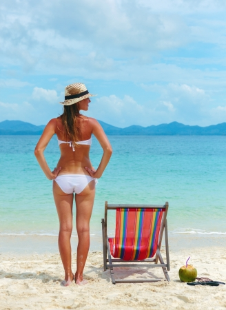 Beautiful Young woman in hat sunbathing on tropical beach photo