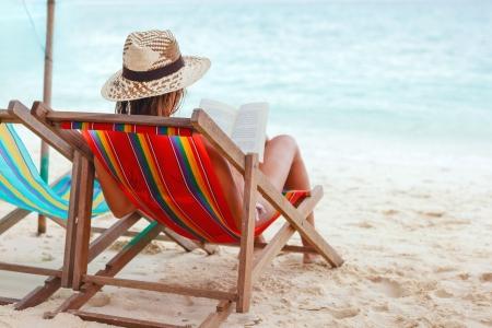 strandstoel: Jonge mooie vrouw zittend op het strand een boek lezen Stockfoto