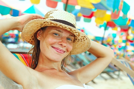 beautiful redhead: Portrait of a happy young woman posing while on the beach