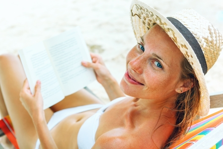 Young beautiful woman sitting on beach reading a book photo