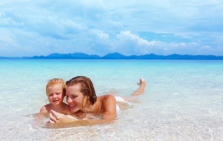 fun in the sun: Mother with little baby girl on summer beach