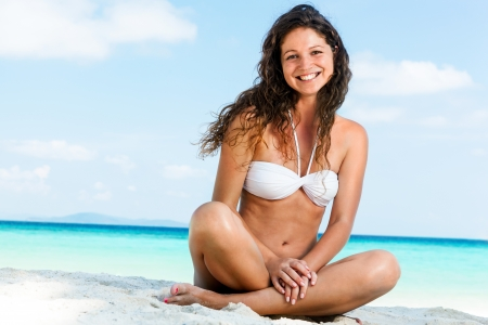 Portrait of a happy young woman posing while on the beach photo