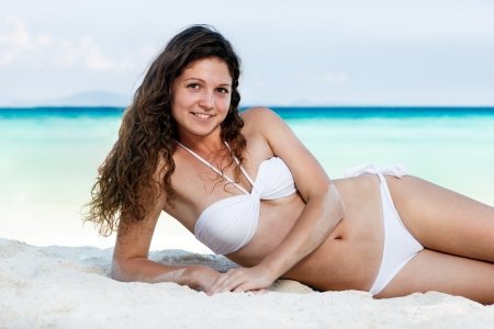 Portrait of a happy young woman posing while on the beach Stock Photo - 17924992