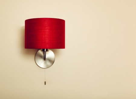 Red lamp on beige wall background