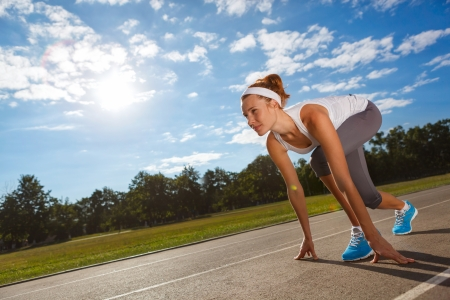 athletic wear: Woman getting ready to start on Stadium - summer outdoors training. Stock Photo