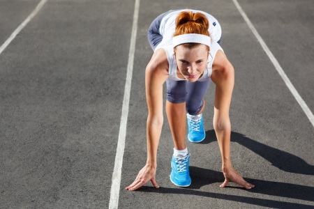 start of race: Mujer a punto de comenzar en el estadio - al aire libre de entrenamiento de verano