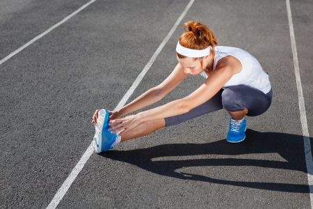 stretching: Female runner stretching before workout - outdoor shot