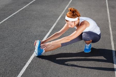 stretching: Mujeres corredor de estiramiento antes del entrenamiento - tiro al aire libre