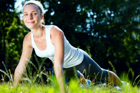 Young woman doing push ups on green grass. photo