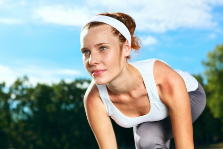 start position: Portrait of Beautiful Woman ready to start running. Stock Photo