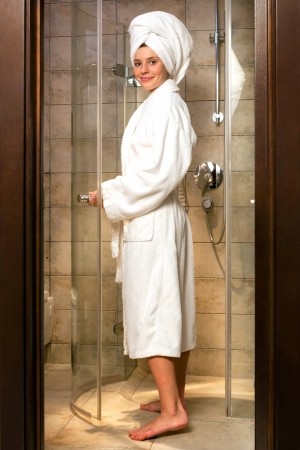 girl with towel: Young woman wearing a white robe in bathroom