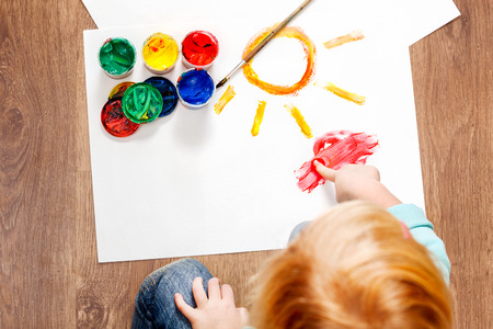 Cute little redhead girl painting with brush. Stock Photo