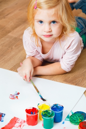 Cute little redhead girl painting with brush. photo