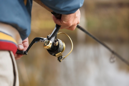 gone: Closeup of Fisherman`s hand with spinning - autumn fishing season. Stock Photo