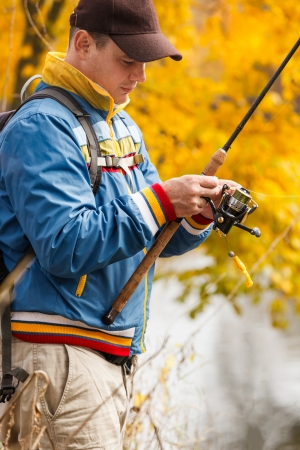 Fisherman with spinning - autumn fishing season. photo