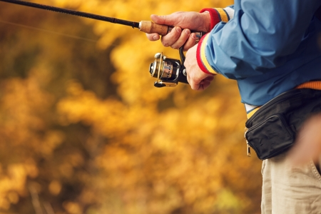 Closeup of Fisherman`s hand with spinning - autumn fishing season. photo