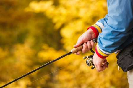 Closeup of Fisherman`s hand with spinning - autumn fishing season. Stock Photo