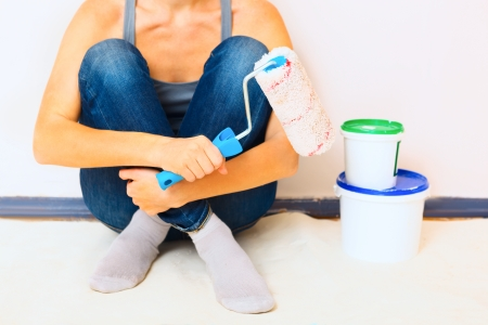 Closeup of woman sitting with paint and brush ready to work photo