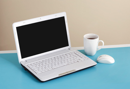 side table: White laptop on table - place for text  Stock Photo
