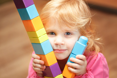 1 year old: Small Girl playing with construction cubes
