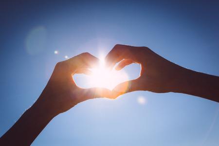haciendo el amor: Manos que hacen el amor, seña, forma en el cielo azul brillante.