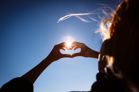 Hands making love shape sign on bright blue sky. Stock Photo