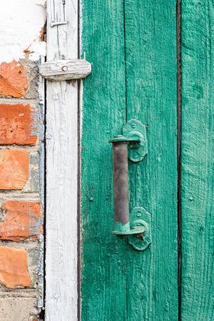green door: Old weathered door with knob. Stock Photo