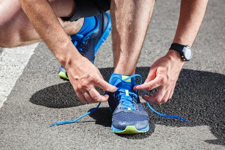 pista de atletismo: Corredor tratando zapatos para correr está preparando para la carrera.