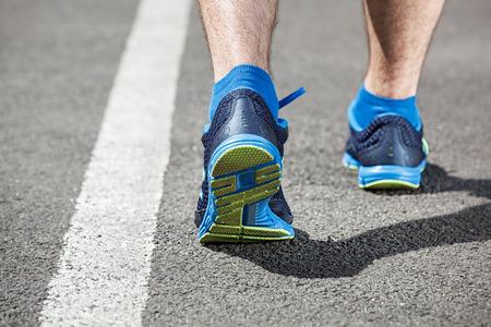 back roads: Runner feet running on stadium closeup on shoe - back view. Stock Photo
