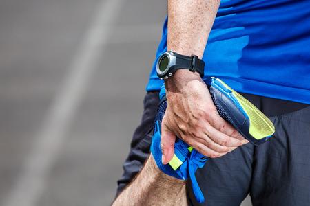 Man runner stretching voor de training.