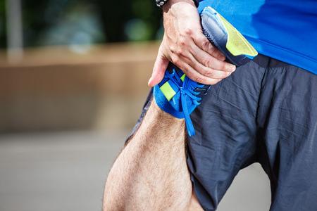 piernas hombre: Atleta masculino estiramiento antes del entrenamiento.