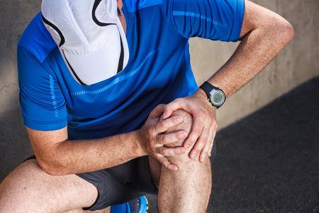 Male runner having problems in knee joint. photo