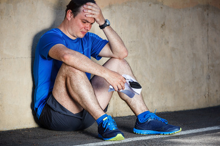 Upset Young male runner resting leaning against wall. photo