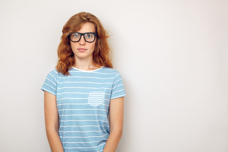 coder: Portrait of Young woman with black glasses standing against wall